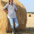 Woman in wellington boots standing in a field of hay — Stock Photo