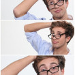 Young man with his glasses askew and hand to his head - Stock Photo
