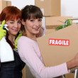 Two girlfriends arranging their new apartment — Stock Photo