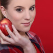 Attractive woman holding a red apple — Stock Photo
