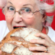 An old lady with hairroller on, biting on a loaf of bread. — Stock Photo