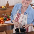 Elderly womcooking in her kitchen — Stock Photo #7456030