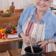 Stock Photo: Elderly womcooking in her kitchen