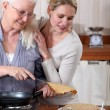 Royalty-Free Stock Photo: A mature mother and her adult daughter making crepes.