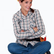 A cute female construction worker sitting on the floor. — Stock Photo
