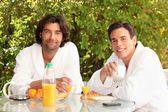 45 years old man and a 20 years old man dressed in bathrobe drinking coffee — Stock Photo