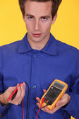 Young man with a multimeter — Stock Photo