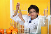 Child playing with a chemistry set and oranges — Stock Photo