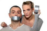 Woman taping-up mans mouth — Stock Photo