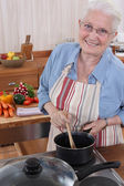 Elderly woman cooking in her kitchen — Stock Photo