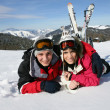Happy boy and girl lying in snow — Stock Photo #7548608