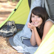 Teenage girl lying down in tent - Stock Photo