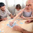 Family completing jigsaw together — Stock Photo #7548988