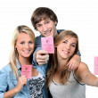 Foto de Stock  : Three teenagers with driving licences
