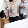 Stock Photo: Couple carrying rolled-up carpet
