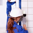 Female electrician fixing wall socket — Stock Photo #7549010