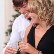 Couple drinking champagne in front of a Christmas tree - Stockfoto