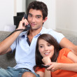 Young couple relaxing on couch, talking on telephone and watching t — Stock Photo #7549067