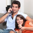 Young couple relaxing on the couch, talking on the telephone and watching t — Stock Photo #7549067