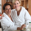 Couple having breakfast in towelling robes — Stock Photo