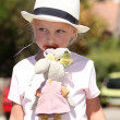 Little girl in a straw hat with a dummy and toy bunny - Stock Photo