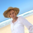 Angled shot of woman in a straw hat on a beautiful sandy beach — Stock Photo