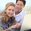 Couple smiling on laptop. — Stock Photo