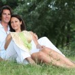 Couple lying on the grass together — Foto de Stock