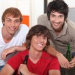 Three friends drinking beer at home — Stock Photo #7549908