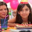Girl celebrating her fifth birthday - Stock Photo