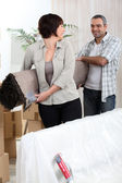 Couple carrying rolled-up carpet — Stock Photo