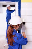 Female electrician fixing wall socket — Stock Photo