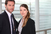 Business couple standing in front of a large window — Stock Photo
