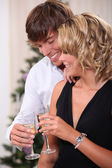 Couple drinking champagne in front of a Christmas tree — Stock Photo