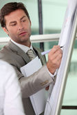 Male executive writing on a full size flipchart — Stock Photo