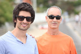 Two men of different generations wearing sunglasses and t-shirts — Stock Photo