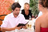 Young man looking at a menu in a restaurant — Stock Photo
