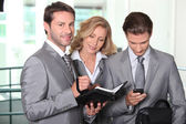 Businessmen and woman checking diary — Stock Photo
