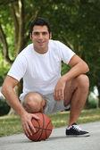 Sepet topu ile çömelerek adam — Stok fotoğraf
