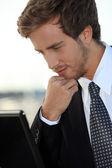 Ejecutivo joven barbudo con un ordenador portátil — Foto de Stock