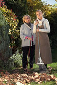 Mother and daughter raking leaves — Stock Photo