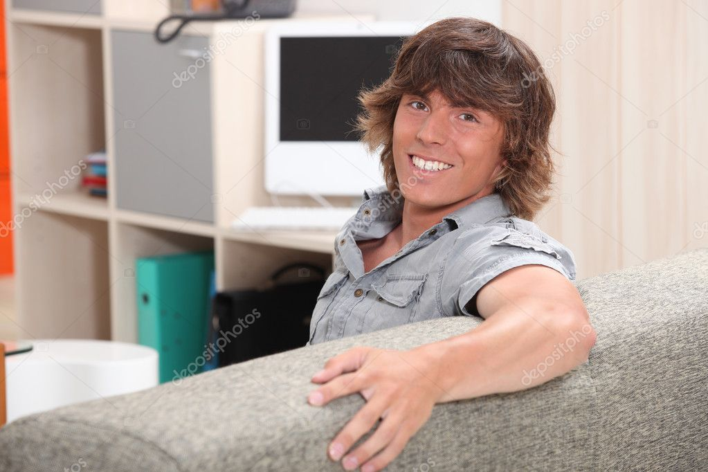Man sitting on a couch and smiling — Stock Photo #7548753