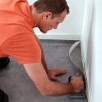 Workman putting down linoleum flooring — Stock Photo #7550093