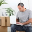Man amid removal boxes working on laptop — Stock Photo #7550100