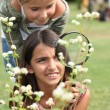 Little girls observing flowers through magnifying glass — Stock Photo