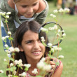 Little girls observing flowers through magnifying glass - Stock Photo
