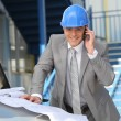 Engineer with architectural plans and cellphone — Stock Photo