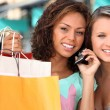 Two young women after shopping, one is calling someone — Stock Photo #7550272