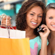 Stock Photo: Two young women after shopping, one is calling someone