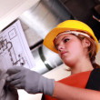 Young female laborer reading plan - Stock Photo